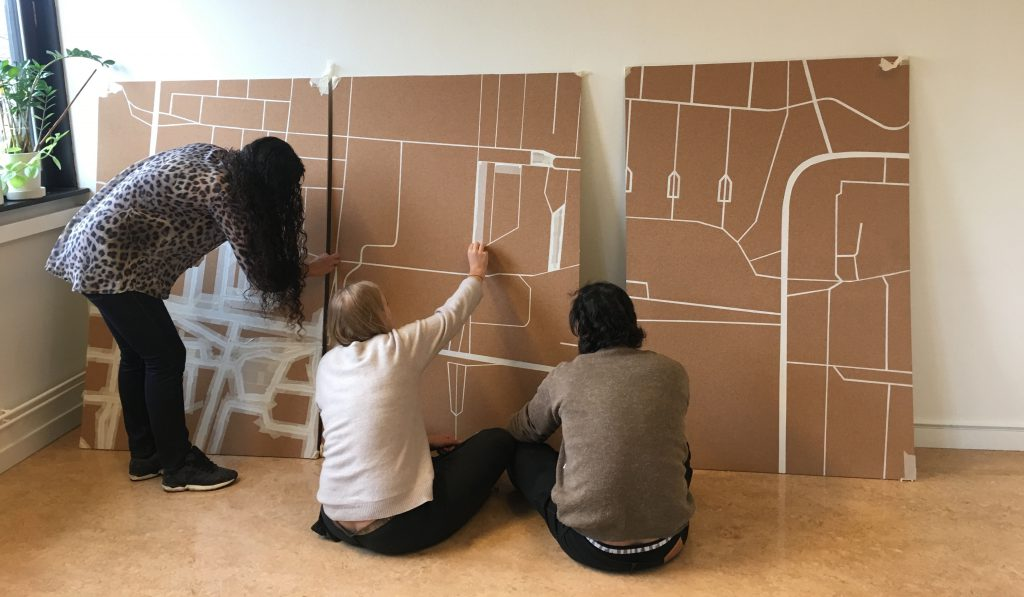 This is us removing the masking tape from the map we painted of Lindängen, together with our stakeholder.